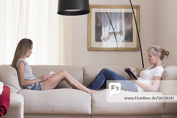Mutter und Tochter sitzend mit digitalem Tablett und Buch auf der Couch
