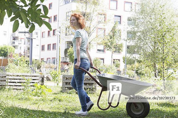 Junge Frau im Garten  städtische Gartenarbeit  Schubkarre
