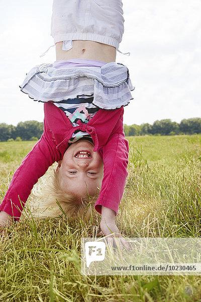 Porträt eines glücklichen kleinen Mädchens beim Handstand auf einer Wiese