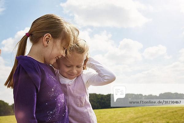 Zwei kleine Mädchen spielen auf einer Wiese