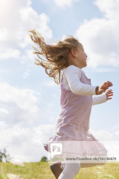 Kleines Mädchen  das auf einer Wiese springt und versucht  Seifenblasen zu fangen. Kleines Mädchen, das auf einer Wiese springt und versucht, Seifenblasen zu fangen.
