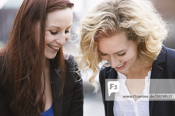Two young women laughing outdoors
