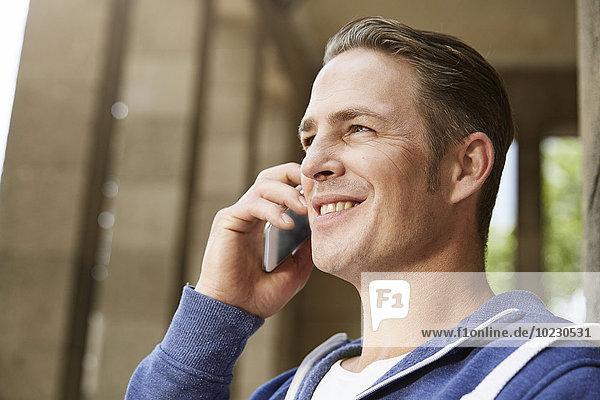 Lächelnder Mann im Freien am Handy