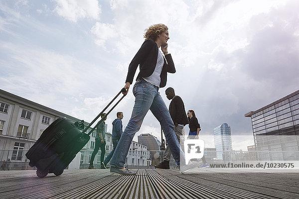 Frau am Telefon  die mit einem rollenden Koffer in der Stadt unterwegs ist.