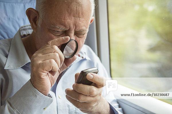 Älterer Mann liest Text auf einem Handy mit Lupe