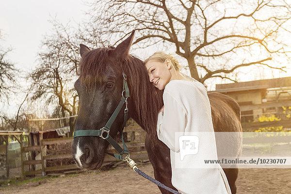 Frau mit Pferd auf der Koppel
