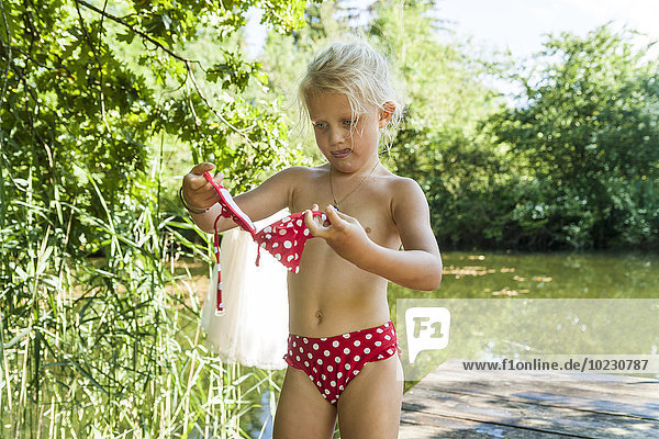 Girl putting on bikini standing on jetty at a lake