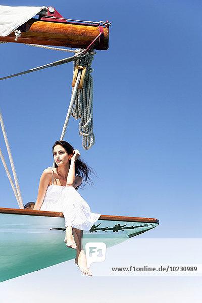 Brünette junge Frau auf einem Segeltörn am Bug sitzend