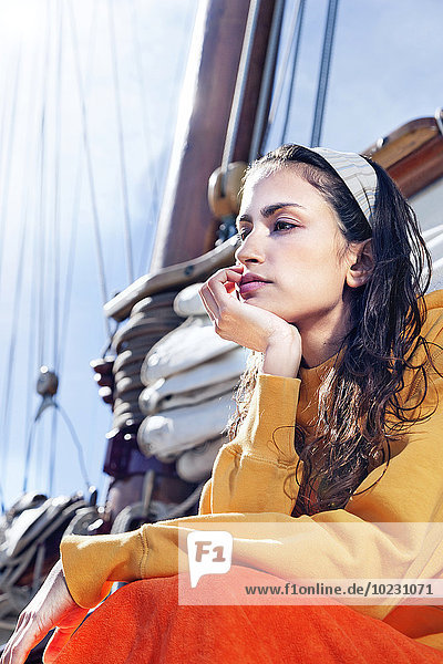 Thoughtful young woman relaxing on a sailing ship
