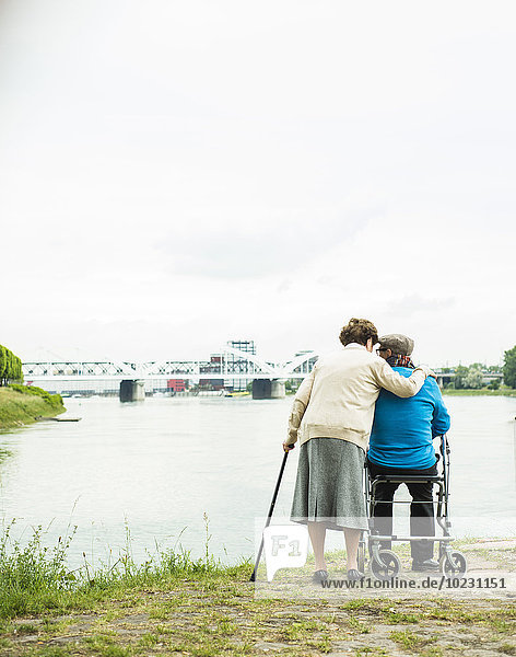 Back view of senior couple standing at water's edge with walking stick and wheeled walker