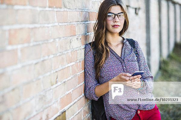 Brünette junge Frau mit Brille hält Handy