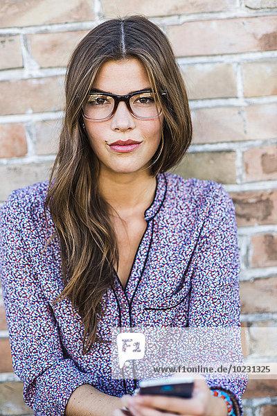 Porträt einer brünetten jungen Frau mit Brille im Freien