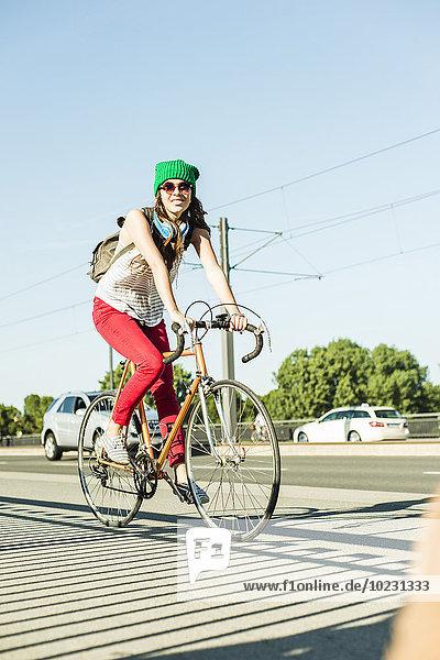 Junge Frau beim Radfahren auf dem Bürgersteig auf der Straße
