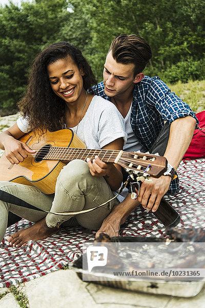 Entspanntes junges Paar beim Gitarrespielen und Grillen im Freien