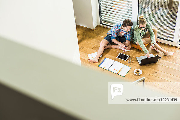 Zwei Schüler sitzen auf dem Holzboden und lernen