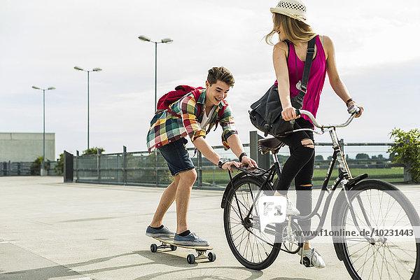 Glückliches junges Paar mit Fahrrad und Skateboard