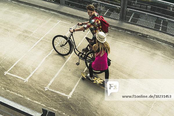 Junges Paar mit Fahrrad und Skateboard