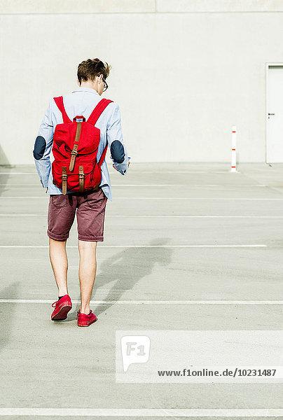 Junger Mann mit Rucksack im Freien auf dem Handy unterwegs