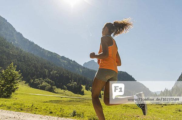 Österreich  Tirol  Tannheimer Tal  junge Frau beim Joggen in alpiner Landschaft