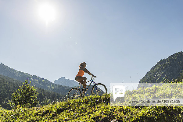 Austria  Tyrol  Tannheim Valley  young woman on mountain bike in alpine landscape