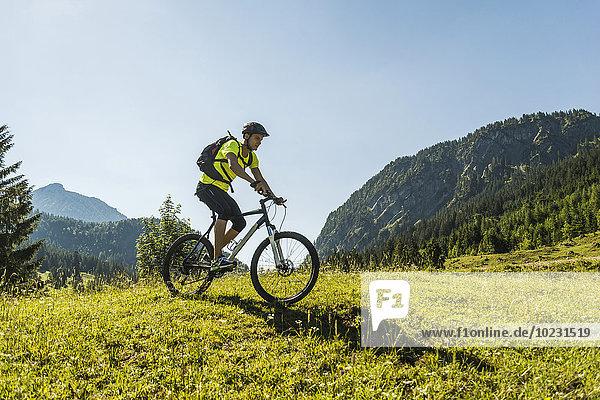 Österreich  Tirol  Tannheimer Tal  junger Mann auf dem Mountainbike in alpiner Landschaft