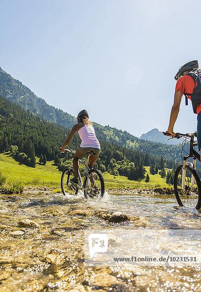 Österreich  Tirol  Tannheimer Tal  junges Paar auf Mountainbikes über den Bach