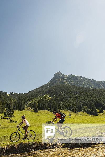 Österreich  Tirol  Tannheimer Tal  junges Paar beim Mountainbiken am Flussufer
