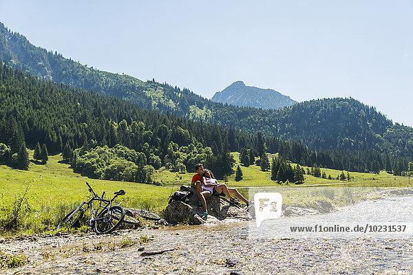 Österreich  Tirol  Tannheimer Tal  junges Paar mit Mountainbikes zum Entspannen am Bach