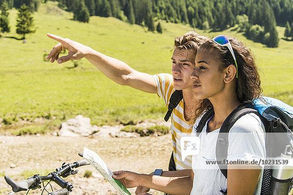 Österreich  Tirol  Tannheimer Tal  junges Paar mit Mountainbike und Karte