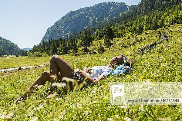 Österreich  Tirol  Tannheimer Tal  junge Frau mit Mountainbike auf der Wiese entspannen