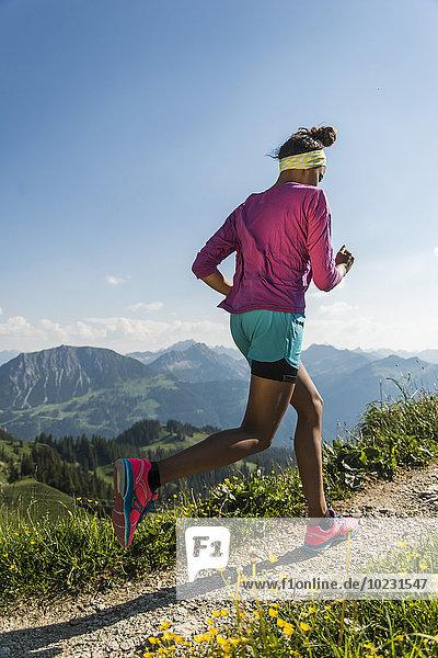 Österreich  Tirol  Tannheimer Tal  junge Frau beim Joggen im Gebirge