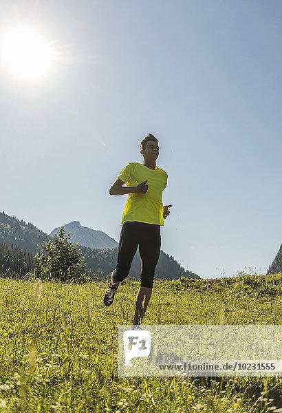 Österreich  Tirol  Tannheimer Tal  junger Mann beim Joggen in alpiner Landschaft