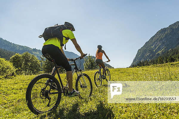 Österreich  Tirol  Tannheimertal  junges Paar auf Mountainbikes in alpiner Landschaft