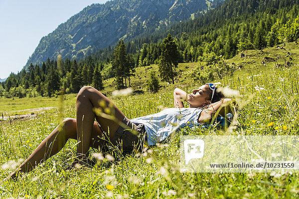 Österreich  Tirol  Tannheimer Tal  junge Frau entspannt auf der Wiese