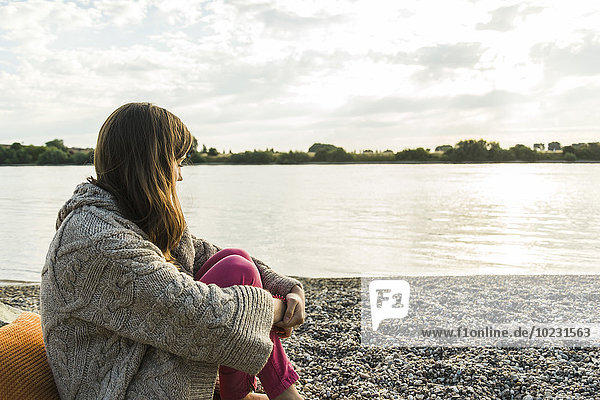 Young woman sitting by the riverside