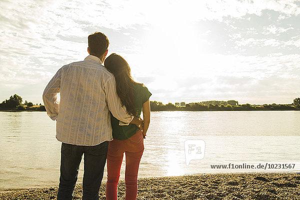 Junges Paar steht am Flussufer