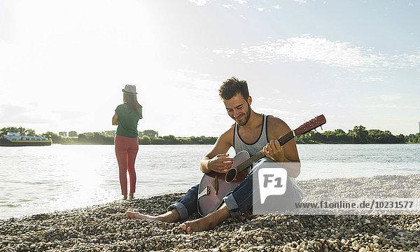 Junger Mann spielt Gitarre mit Frau am Flussufer