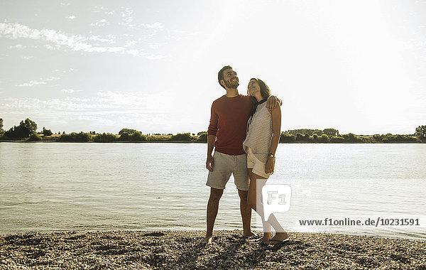Junges Paar  das am Flussufer spazieren geht