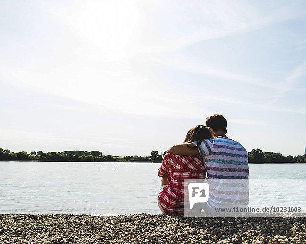 Junges Paar am Flussufer sitzend