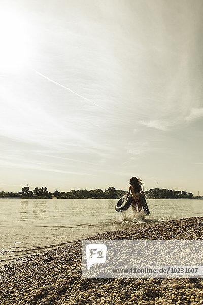 Junge Frau läuft mit Schläuchen im Fluss
