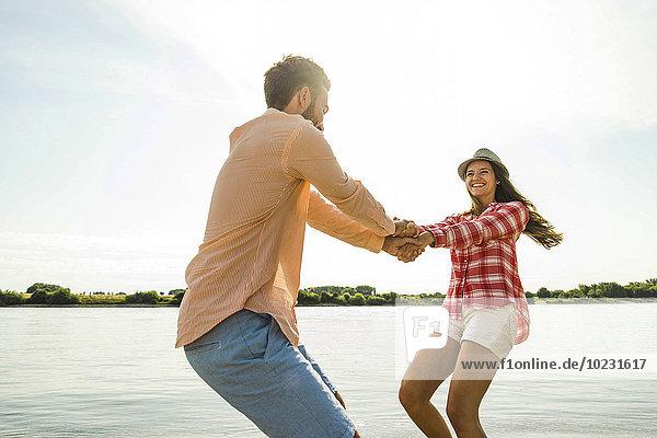 Unbeschwertes junges Paar Hand in Hand am Fluss