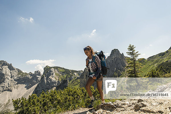Österreich  Tirol  Tannheimer Tal  junge Frau beim Wandern auf dem Bergweg