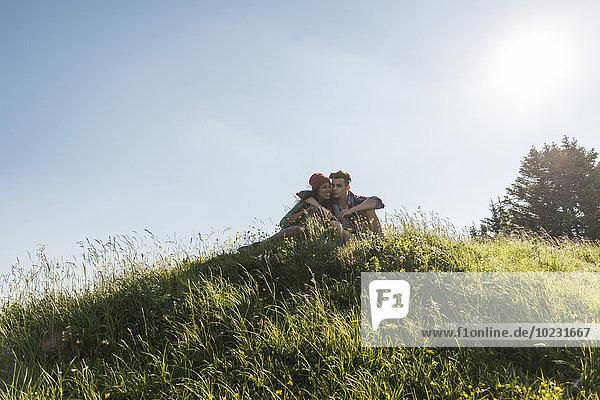 Österreich  Tirol  Tannheimer Tal  junges Paar umarmt auf der Alm