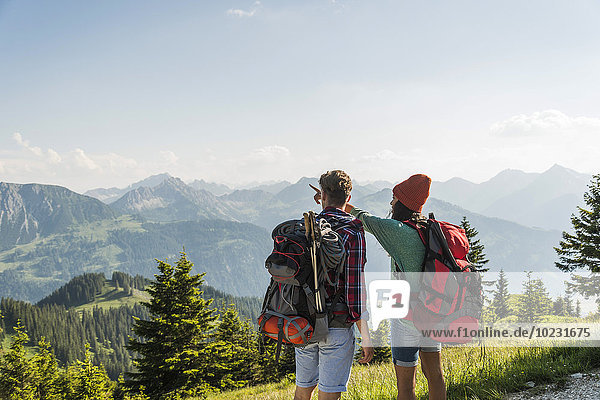 Austria  Tyrol  Tannheimer Tal  young couple in alpine landscape looking at view