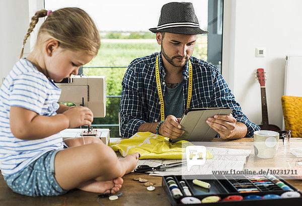Vater mit digitalem Tablett und Tochter beim Nähen zu Hause