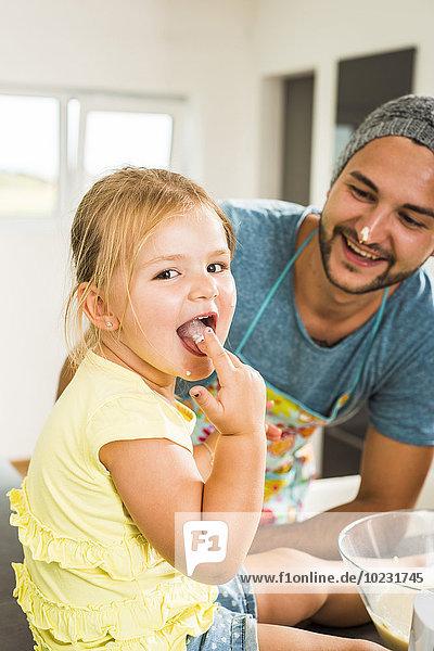 Vater und Tochter backen in der Küche Teig probieren