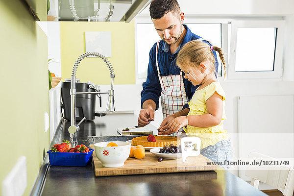 Vater und Tochter in der Küche bei der Zubereitung von Obstkuchen