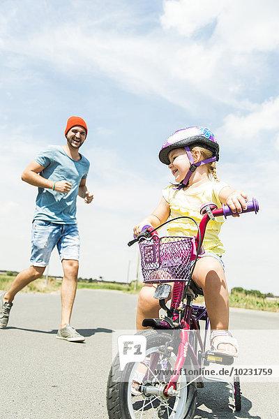 Vater begleitet Tochter auf dem Fahrrad