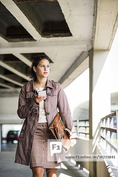 Junge Frau mit Smartphone im Parkhaus