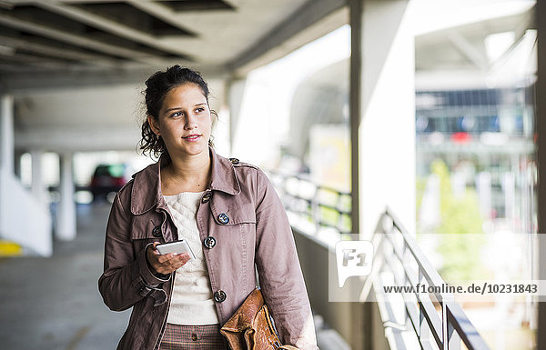 Young woman using smart phone in parking garage